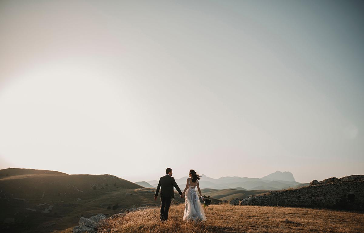 Mariés de dos marchant sur une colline